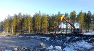 Kaivinkoneen pitkä puomi toimii laajan vesialueen rakentamisessa hyvin.